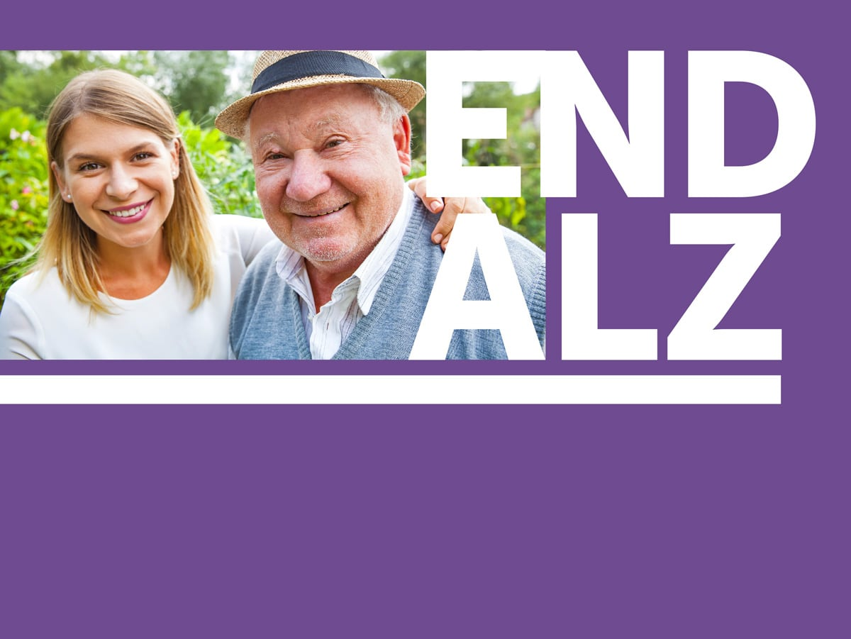 """A woman and her older father, with the words """"End Alz."""""""